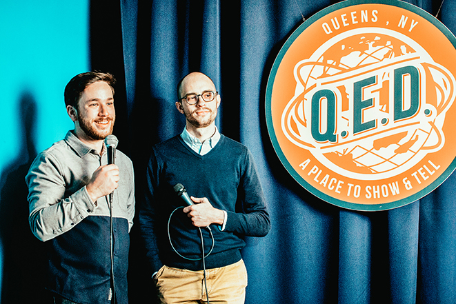 Patrick Cartelli and Evan Barden holding microphones on the QED stage.
